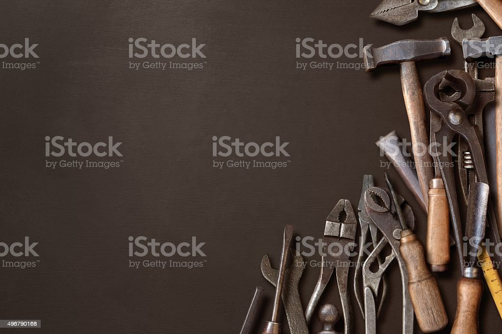 Messy workshop hand tools piled on a black blackboard side stock photo