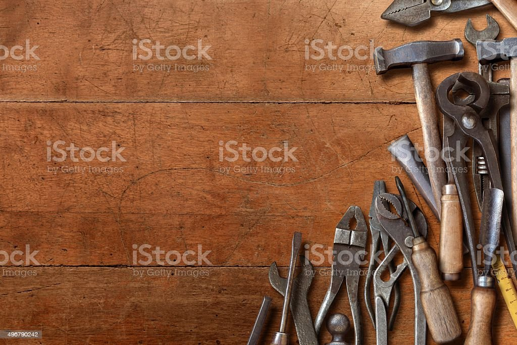 Messy workshop hand tools piled on a wooden desk side stock photo