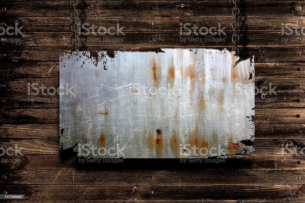 Metal banner held with chains on a grungy background royalty-free stock photo