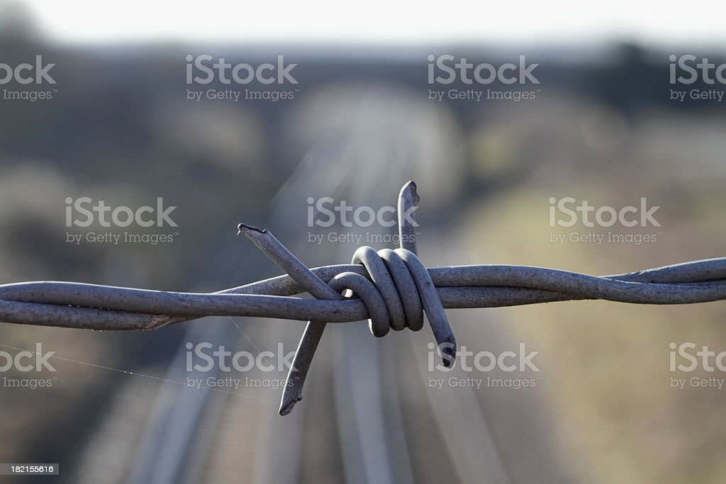 Metal barbed wire close up with distant railway bridge royalty-free stock photo