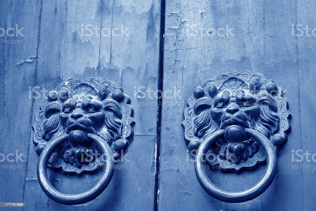 Metal beast head on the door panels in Phoenix Town royalty-free stock photo