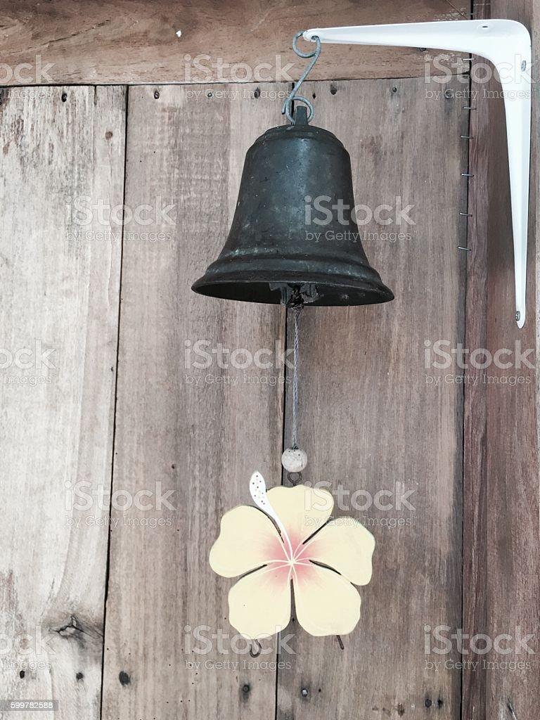 Metal bell hanging on the corner of the wooden door royalty-free stock photo