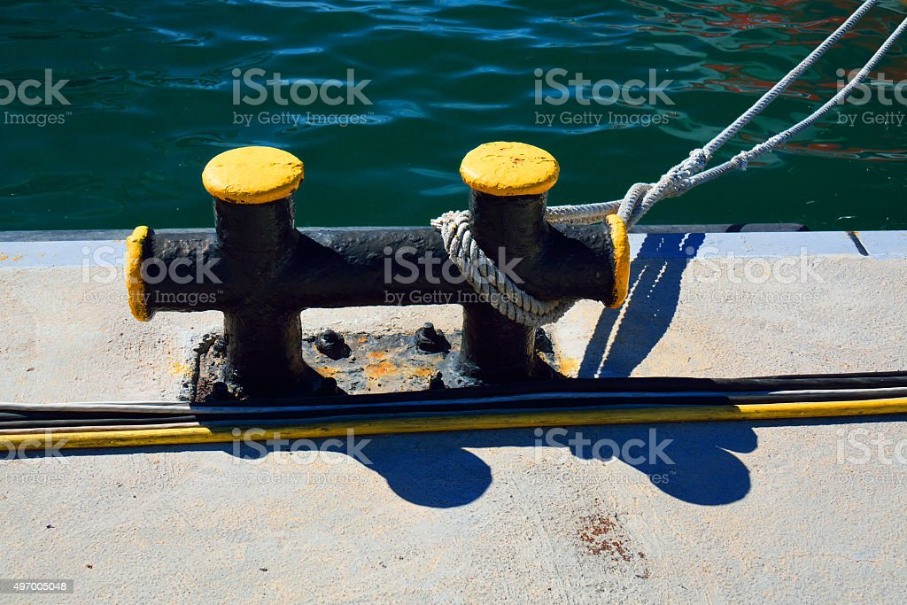 metal bitt on a pier with a mooring line stock photo