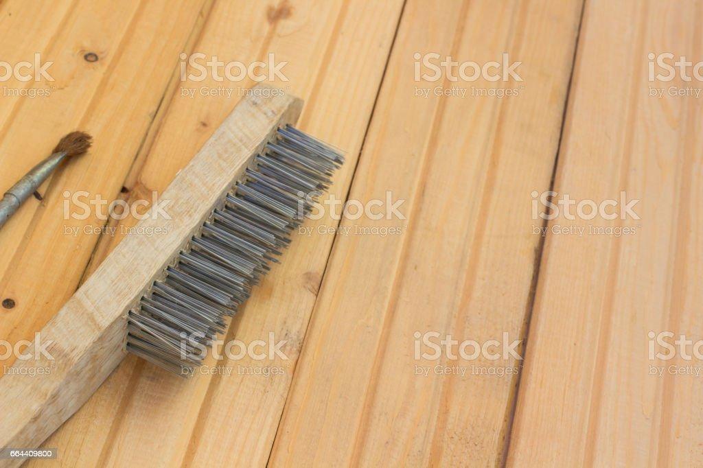 Metal brush for repair on the wooden floor stock photo