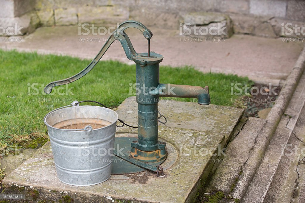 Metal bucket and well pump sat in a rural setting stock photo