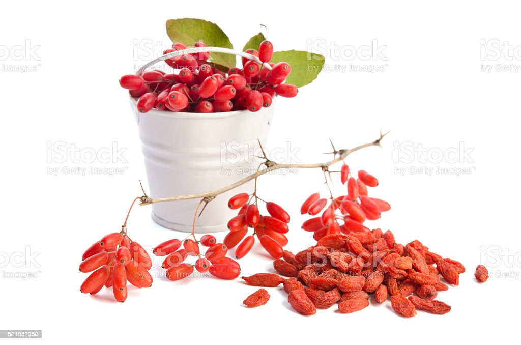 metal bucket with barberries near heap of goji berries stock photo