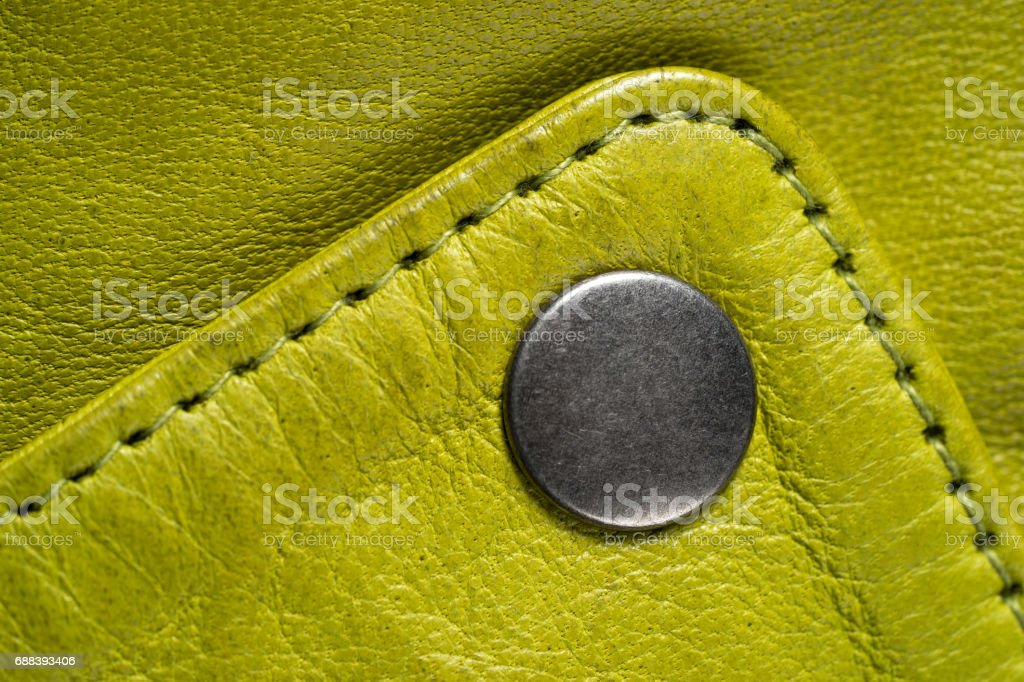 Metal button on green color leather jacket. Lime color. Macro leather jacket detail. stock photo