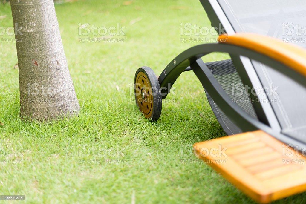Metal chaise-longue on green grass near tree. stock photo