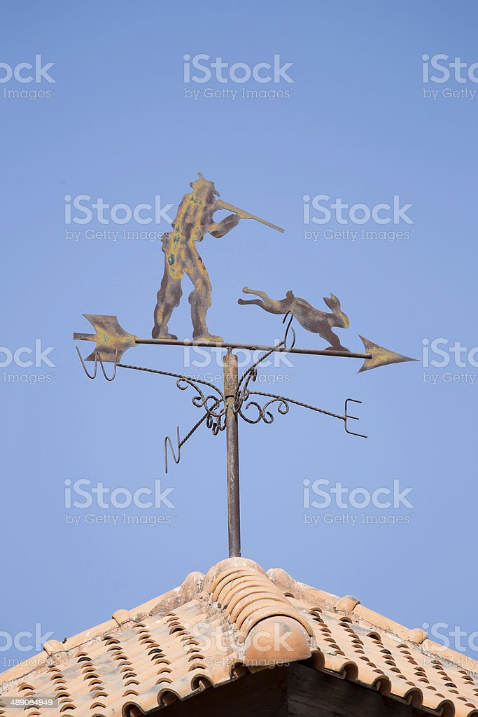 metal chaser and rabbit weather vane on a roof. royalty-free stock photo