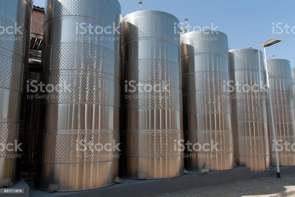 Metal chrome cask for wine photo. Stainless steel pipes and barrels as part of winery equipment stock photo