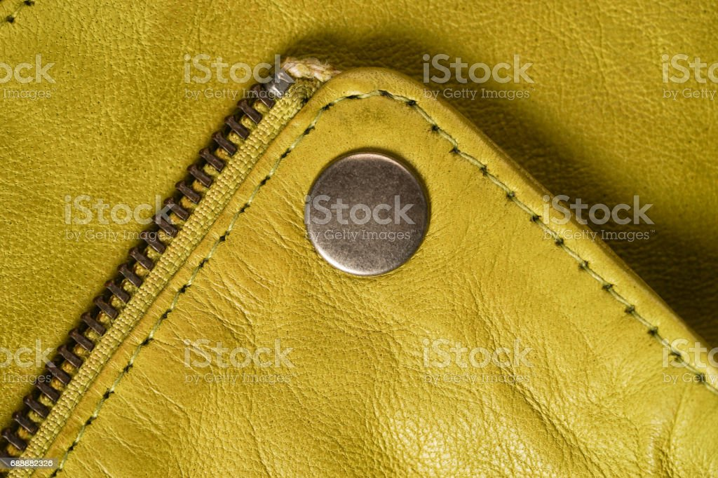 Metal clasp button on yellow leather jacket. macro detail stock photo