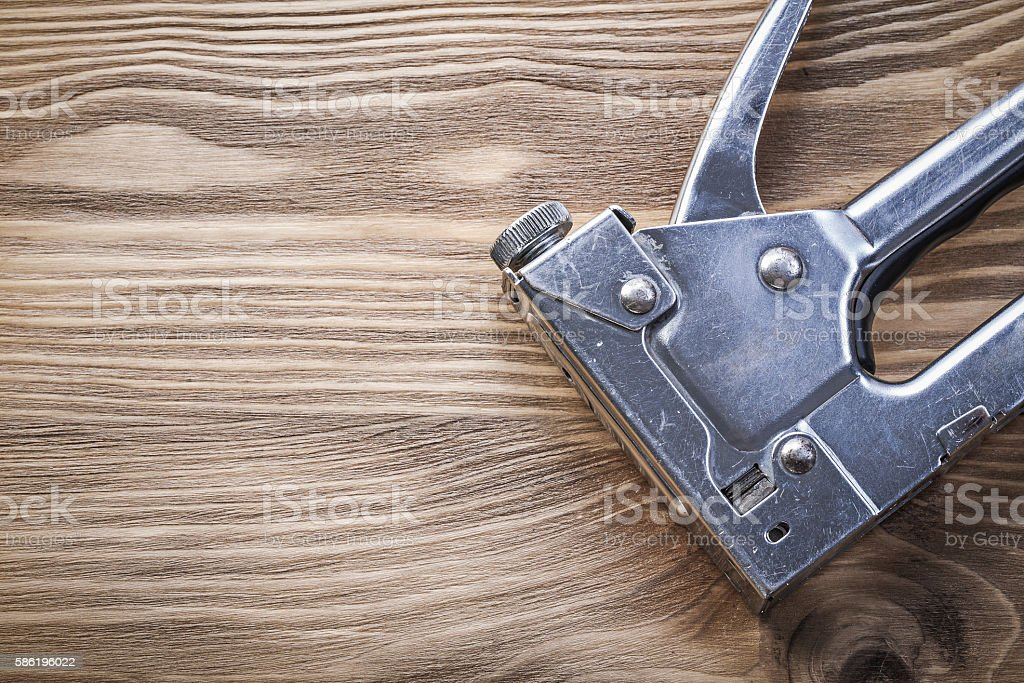 Metal construction stapler on wooden board copy space stock photo