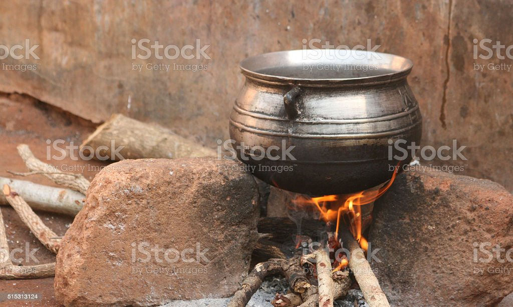 Metal cooking cauldron over open wood fire stock photo