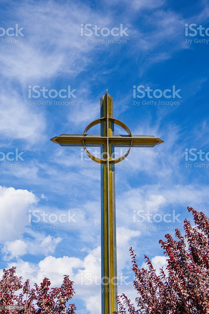 Metal cross against a blue sky with clouds (P) royalty-free stock photo