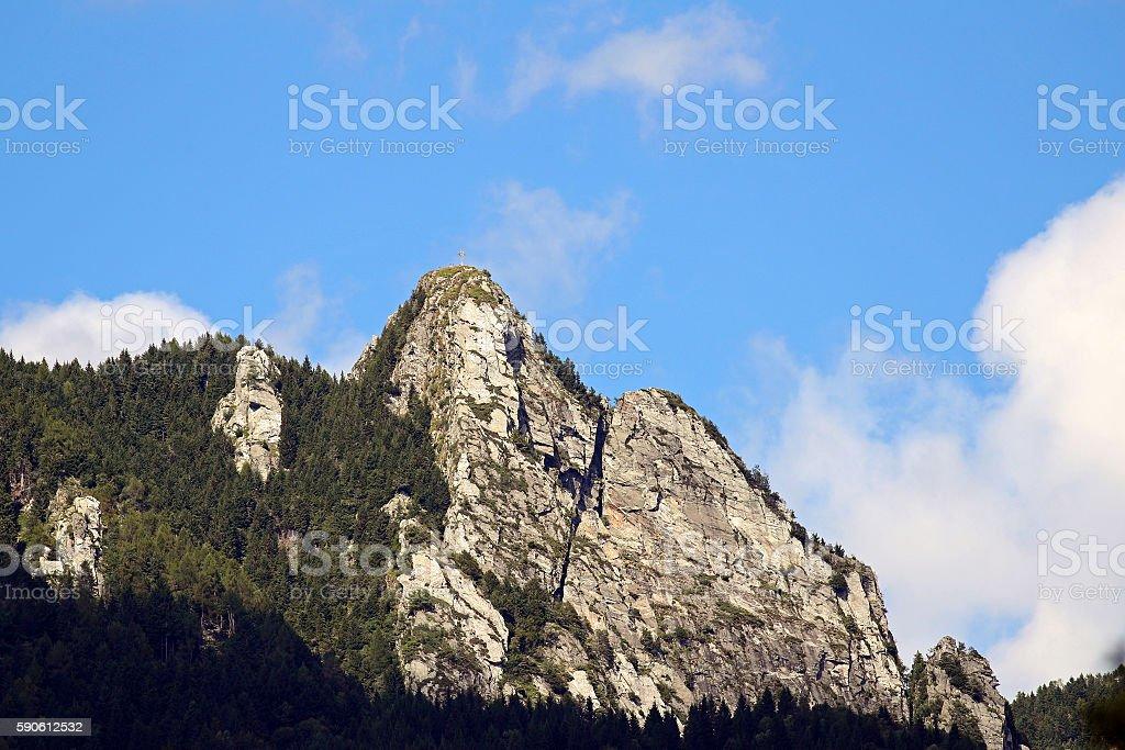 Metal cross on a mountain peak stock photo