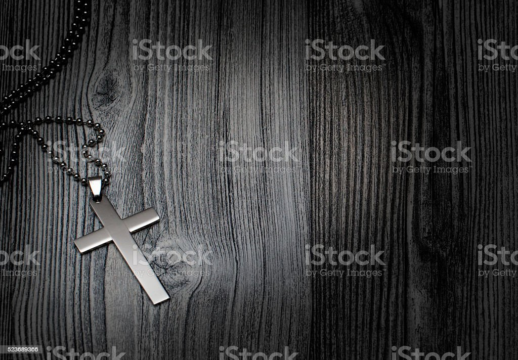 Metal cross on a wooden background stock photo