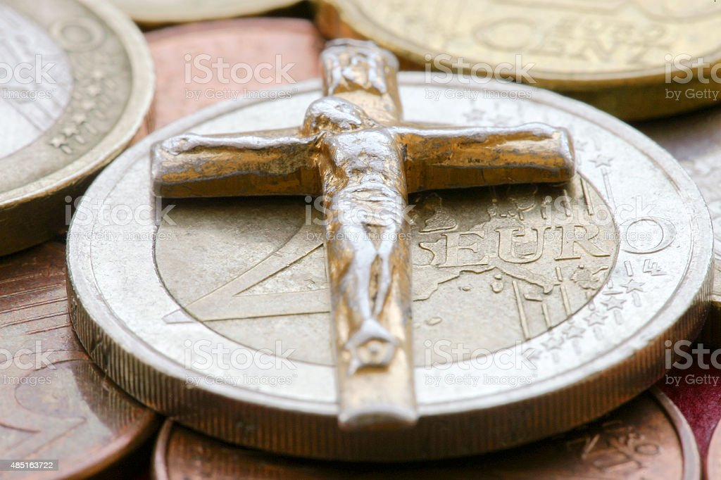 Metal cross on the euro coins stock photo