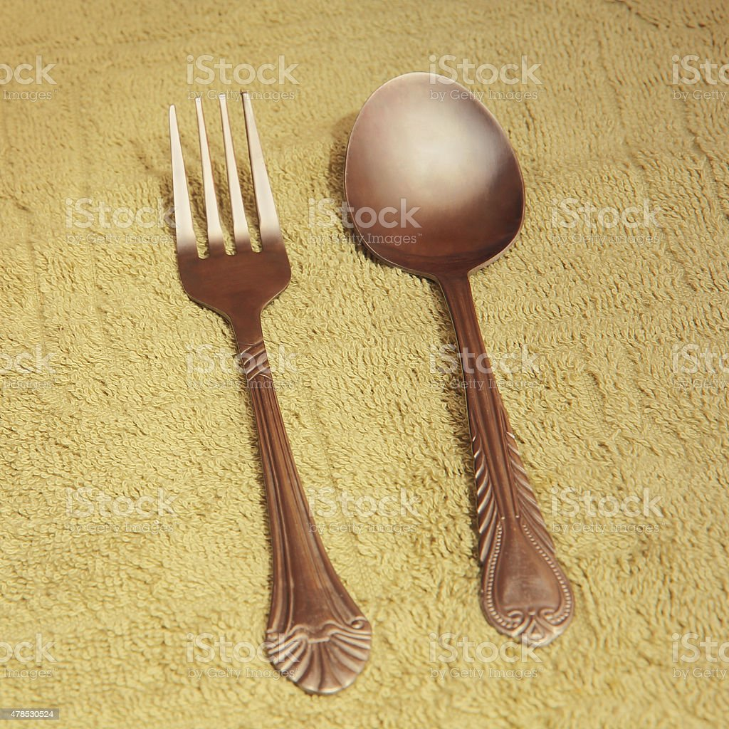 Metal cutlery on taupe fabric background. stock photo