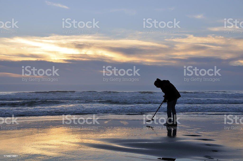 Metal detecting at sunset stock photo
