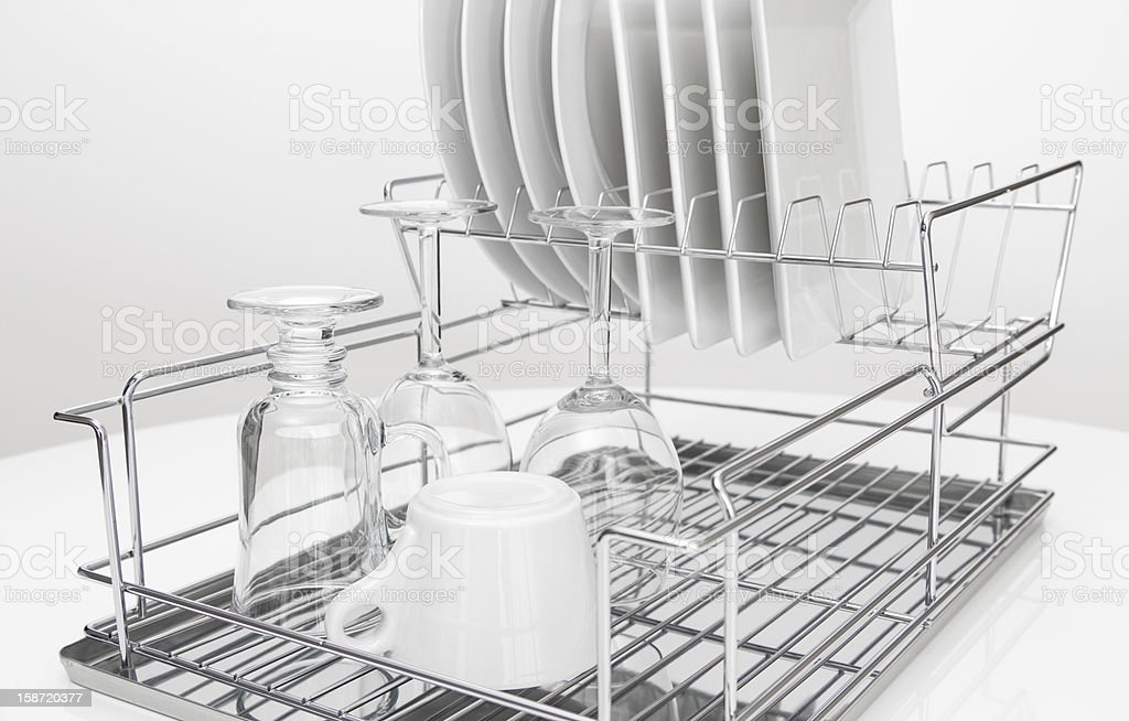 Metal dish rack with dishes and glasses stock photo