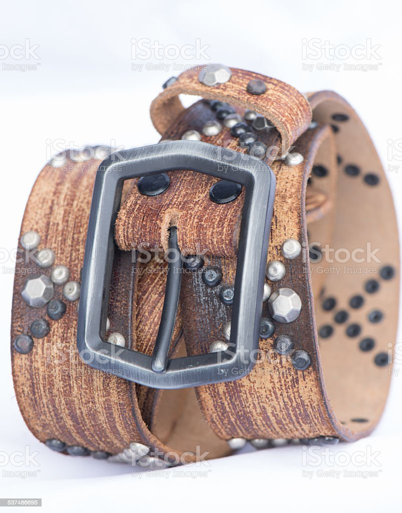 metal dots cross on brown leather belt stock photo