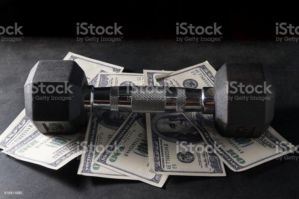 Metal dumbbell on money. stock photo