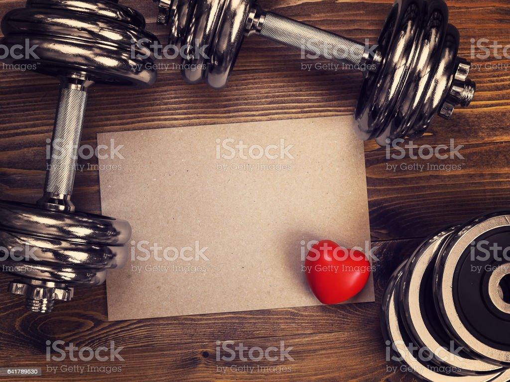 metal dumbbells and red heart on a wooden background stock photo