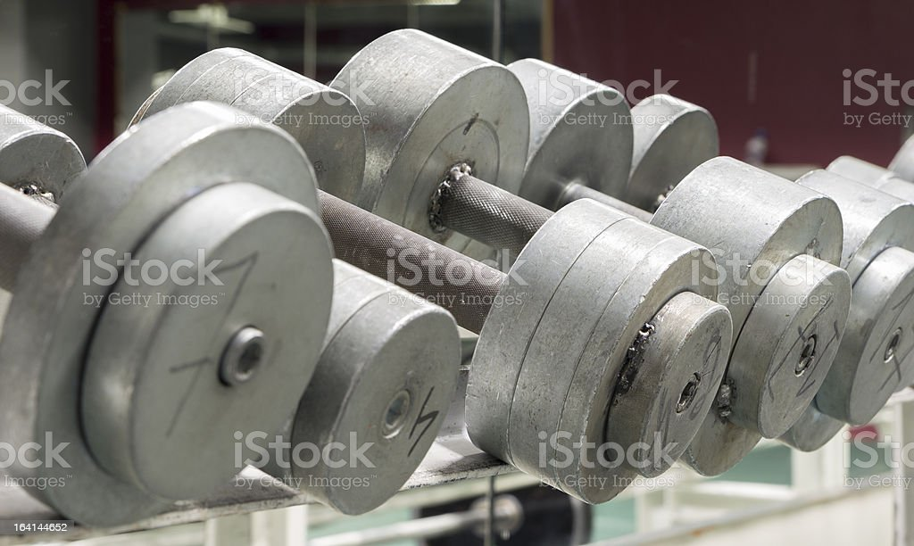 Metal dumbbells on an old rusty rack royalty-free stock photo
