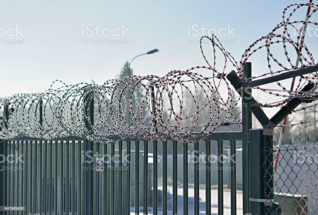 Metal fence with a sharp barbed wire on the top stock photo