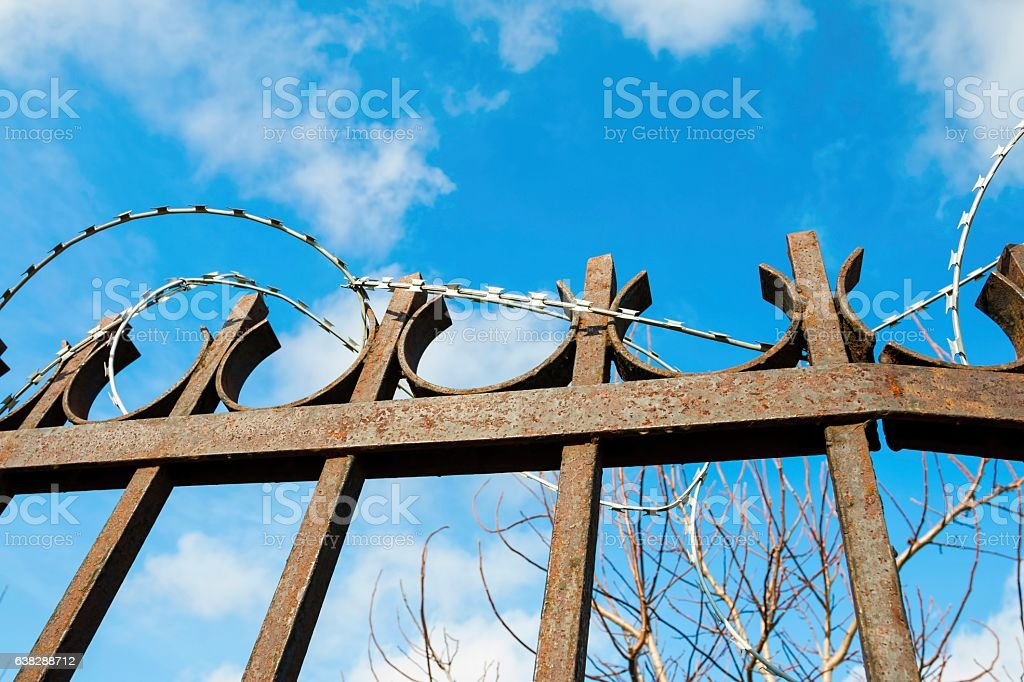 Metal fence with barbed wire against the sky. stock photo