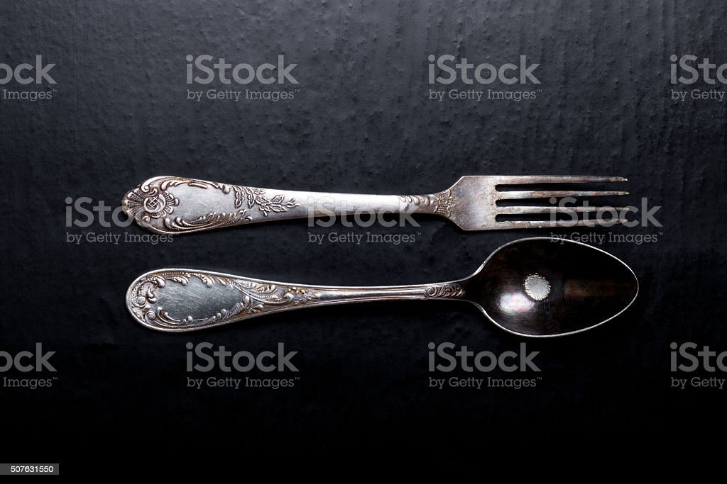 Metal fork and spoon on a black background stock photo