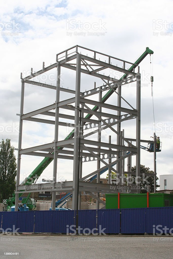 Metal frame of new building and cherry picker stock photo