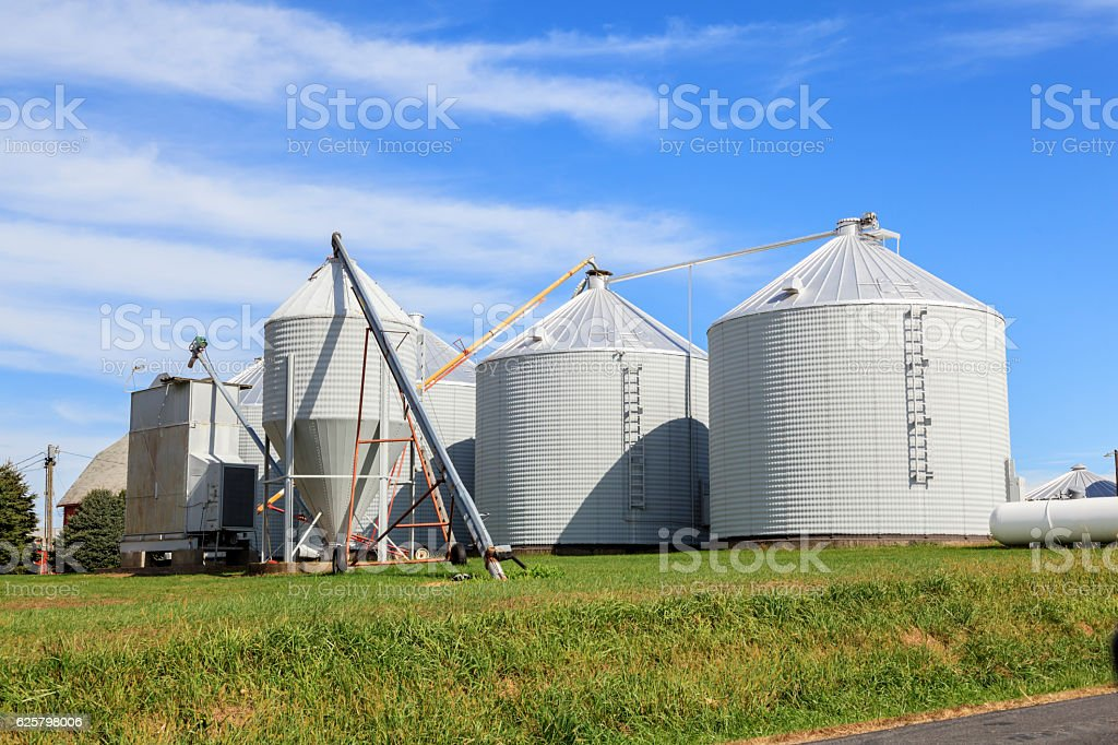Metal grain bins and augers stock photo