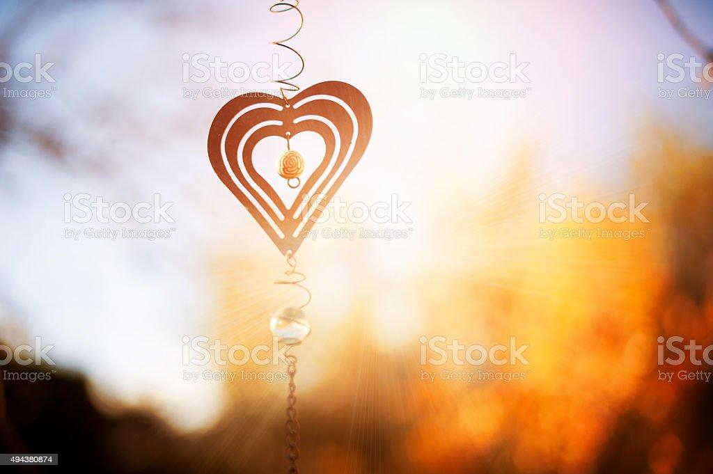 metal heart pendant at sunset stock photo