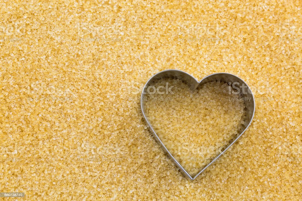 Metal heart shaped cookie cutter on unrefined unbleached Crystalline sugar in crystal brown color stock photo