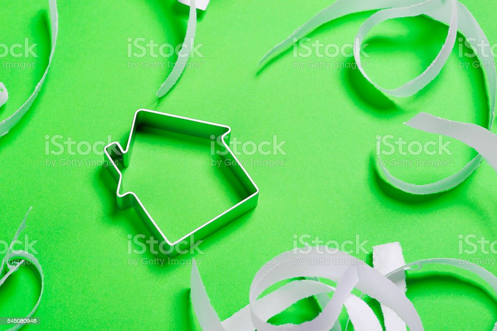 Metal house standing on a green surface stock photo