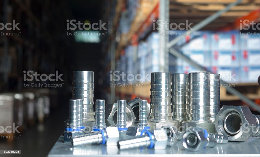 Metal hydraulic fittings stands on the silver table stock photo