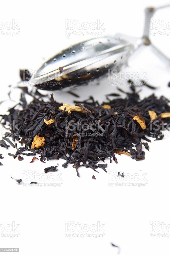 Metal infuser and black Tea leaves stock photo