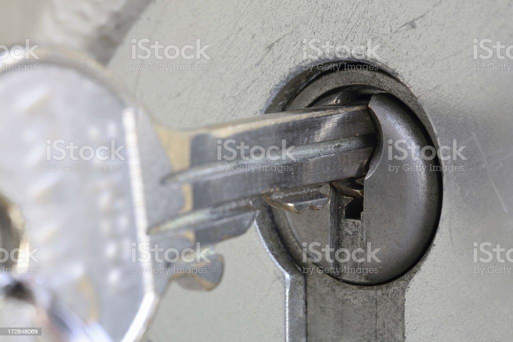 Metal key being put into an outdoor lock, macro close-up stock photo