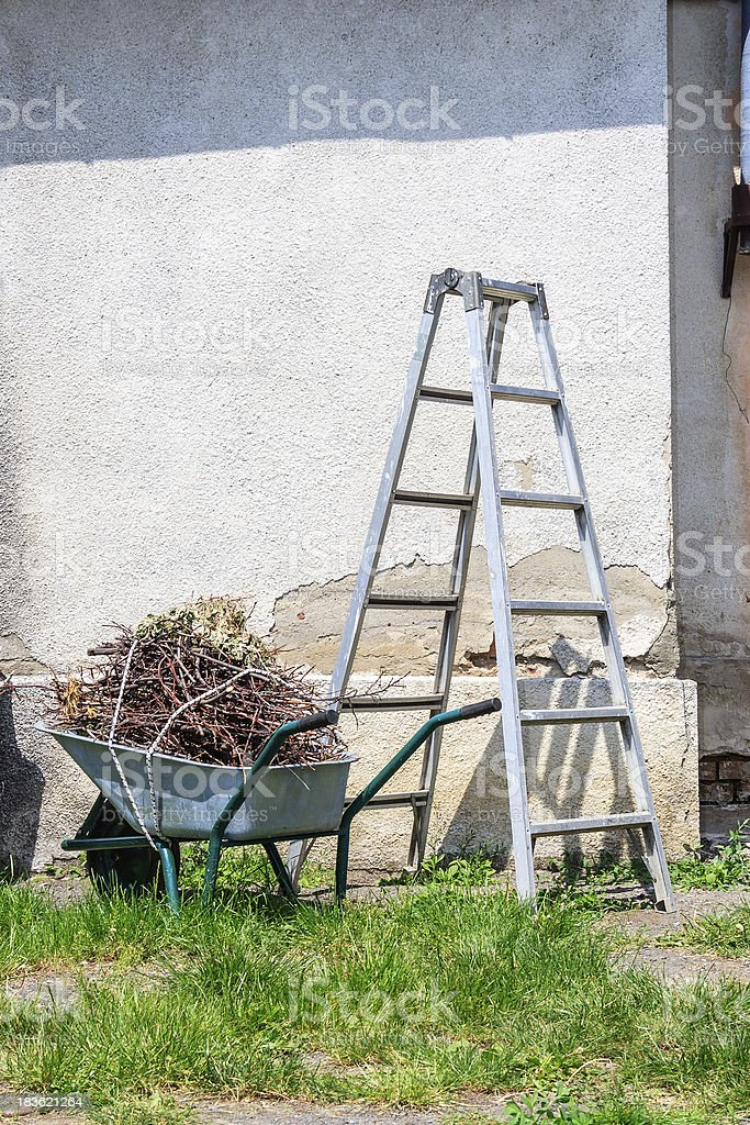 metal ladder and a wheelbarrow by the old wall royalty-free stock photo