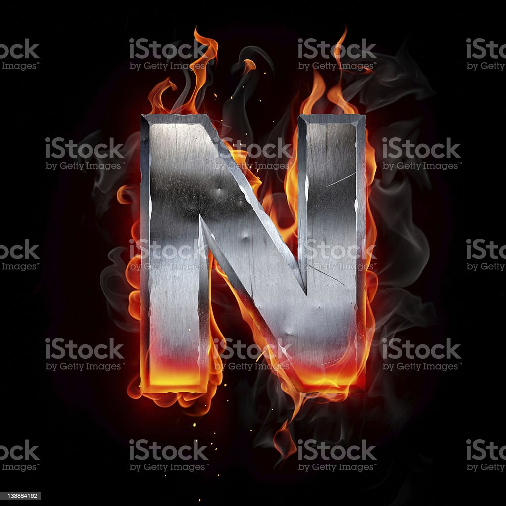 Metal letter N ablaze in flames against a black background royalty-free stock photo