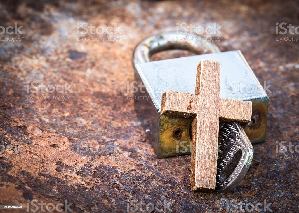 metal lock and key with wooden cross stock photo