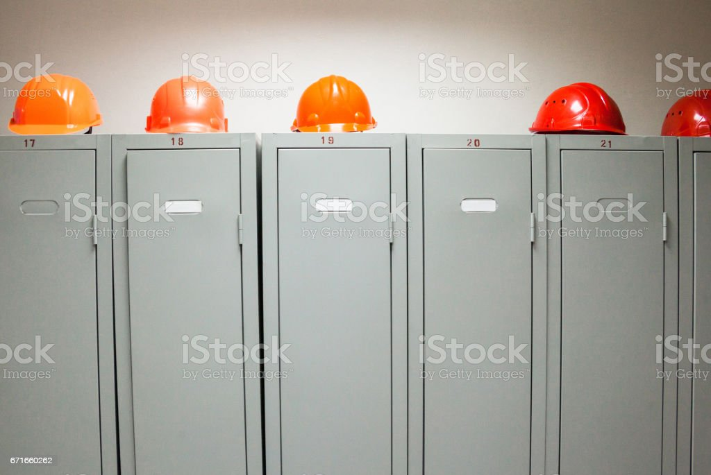 Metal lockers and plastic hard hats stock photo