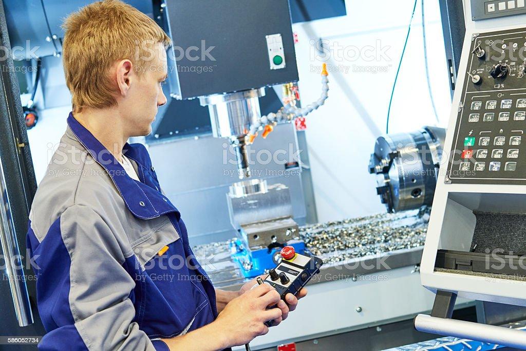 metal machining industry. Worker operating cnc milling machine stock photo