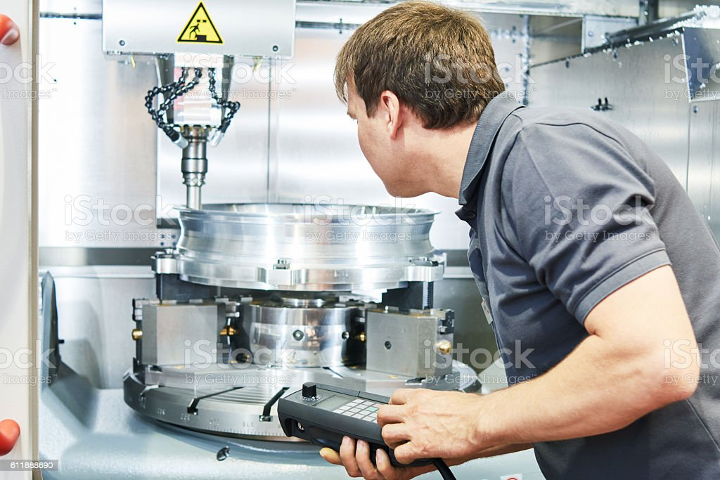 metal machining industry. Worker operating cnc milling machine stock photo