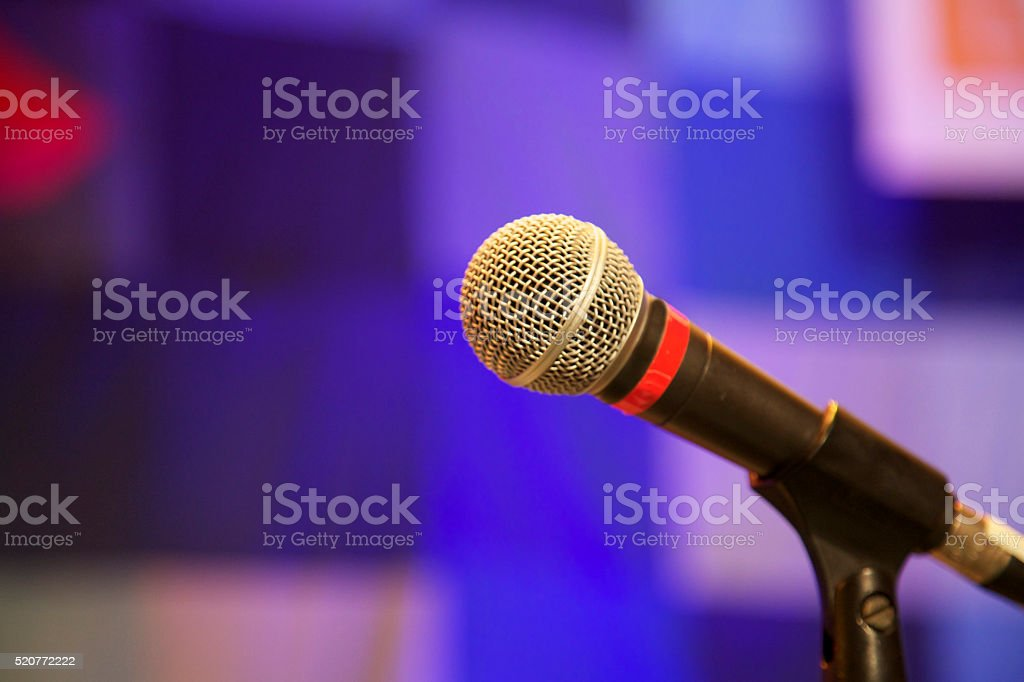 metal microphone at concert on stage with abstract blue background stock photo