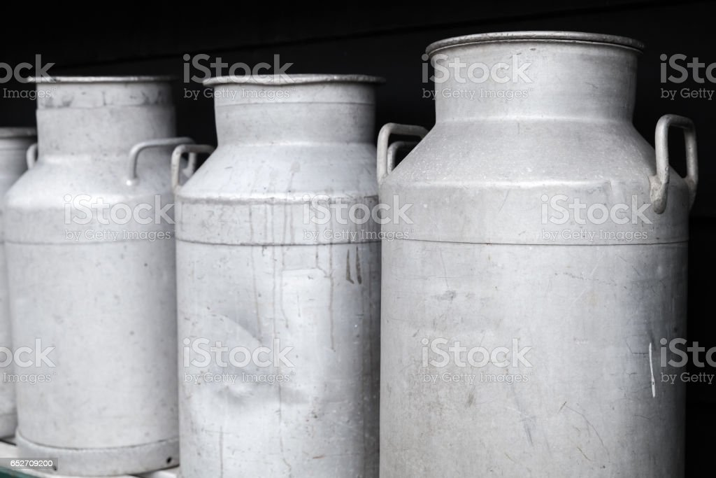 Metal milk churns stand in a row, close up stock photo