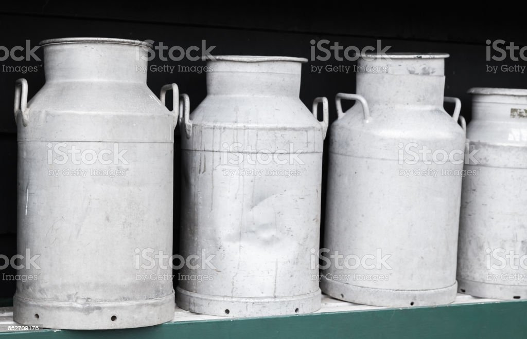 Metal milk churns stand in row stock photo