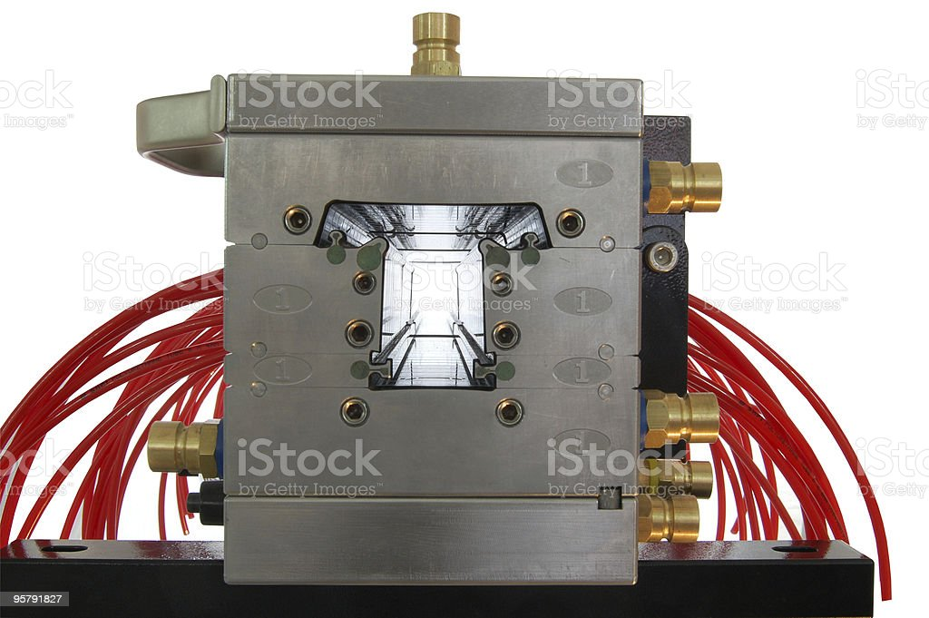 Metal mold extruding red plastic stock photo