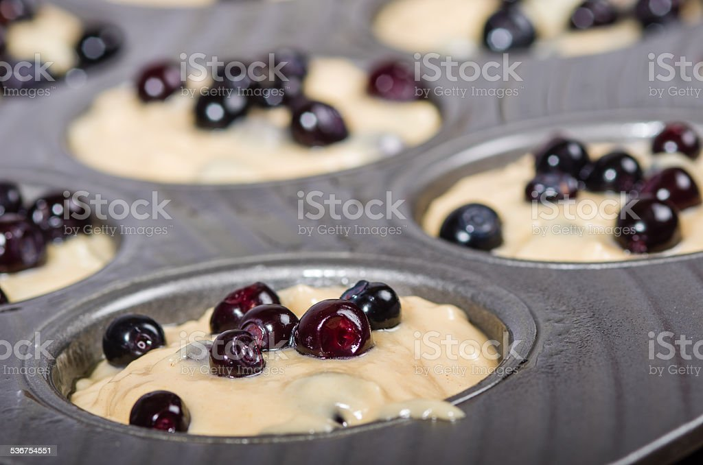 Metal muffin pan with batter and berries stock photo